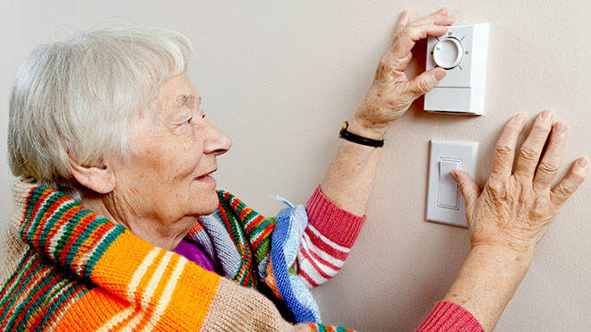Energy smart woman checking thermostat